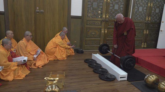 年近90歲的聖僧開初教尊用他三根手指頭已骨節折斷變形的右手,單手拿起了200磅金剛杵上基座,展顯了其上超十六段的聖力,遠超亞洲第一大力士,驚駭世人。 (攝影:楊慧君) 「拿杵上座」是佛教界鑒別真假佛法、真假聖者最直截了當的檢測器。 金剛大力王拿杵上座的標準是上超30段,為最高頂峰,也就是說歷史上無論什麼大力士王牌或等妙覺巨聖德上超30段,就是最高頂峰了,而南無第三世多杰羌佛竟然單手拿起上超了56段的鎮殿金剛杵超過了13秒鐘,其重量是420磅,成為世界上史無前例的拿杵金剛大力王,聖德們說南無羌佛拿杵上座的紀錄是前無古人、也敢預言是後無來者真正佛陀的本質。